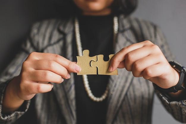 Mani della donna di affari che collegano il pezzo di puzzle con sfondo sfocato