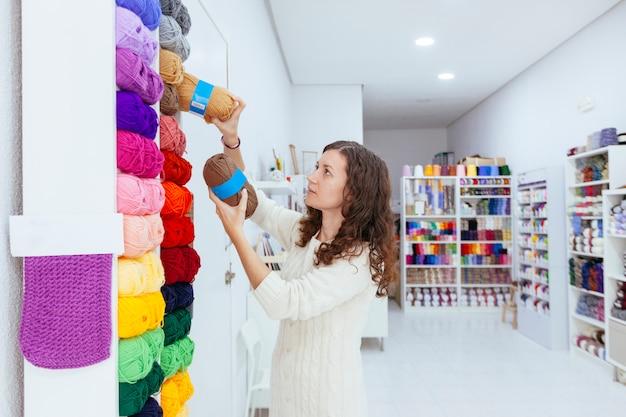 Donna d'affari nel suo negozio al dettaglio raccogliendo filati di lana