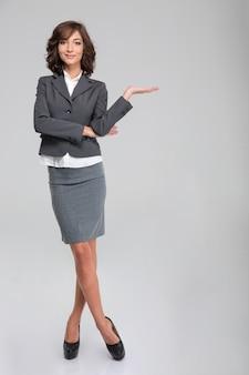 Copyspace hoding della donna di affari sulla palma sopra la parete bianca