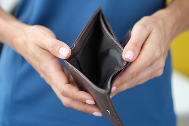 Donna di affari che tiene portafoglio aperto vuoto in primo piano delle mani