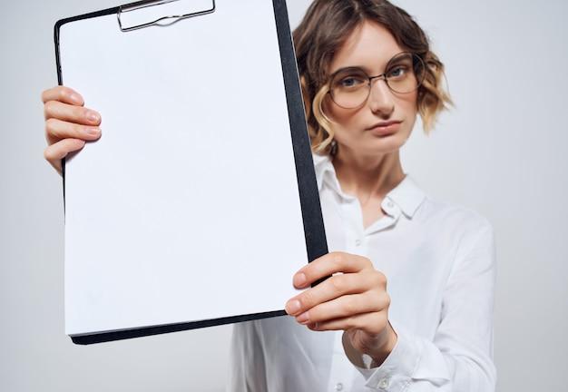 Donna d'affari che tiene in mano cartella foglio bianco copia spazio ufficio