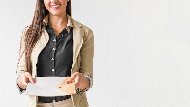 Carte della tenuta della donna di affari con fondo bianco