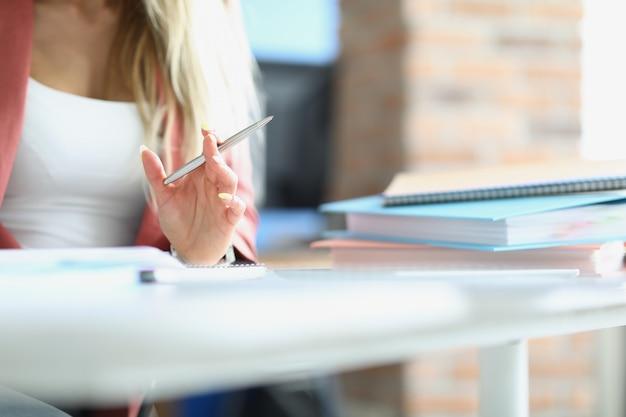 Donna d'affari che tiene la penna a sfera d'argento al tavolo con il primo piano delle cartelle