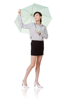 Donna di affari che tiene ombrello di verde, isolato sul muro bianco.