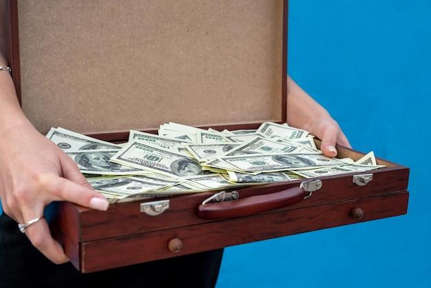 Donna d'affari che tiene in mano una valigia di legno piena di dollari dopo un accordo di successo o un grande vincitore su sfondo blu