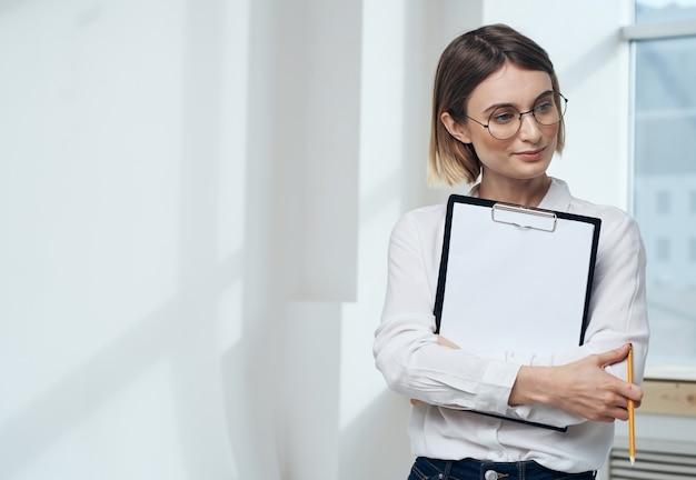 Donna d'affari al chiuso con mockup foglio bianco cartella documenti
