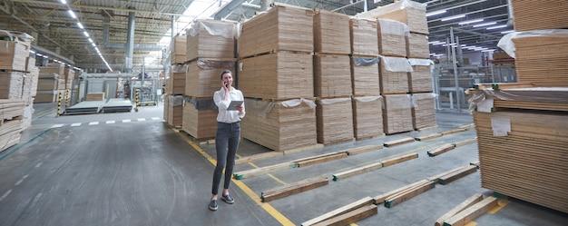 Donna d'affari in fabbrica di carpenteria industriale - produzione di tavole di legno con macchine moderne