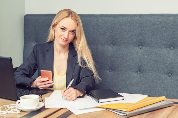 La donna di affari sta tenendo lo smartphone e scrive su uno spazio in bianco all'ufficio