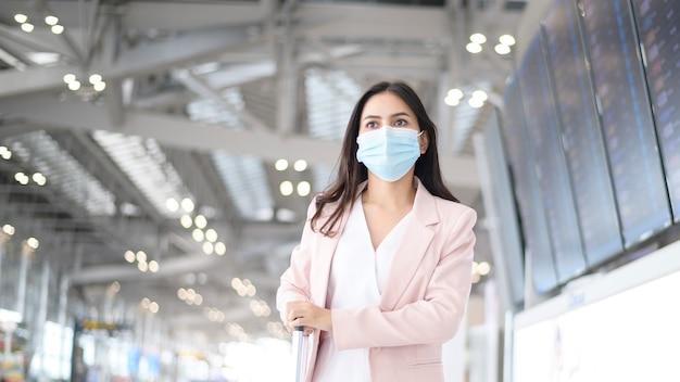 Una donna d'affari indossa una maschera protettiva in aeroporto internazionale, viaggi sotto pandemia covid-19, viaggi di sicurezza, protocollo di allontanamento sociale, nuovo concetto di viaggio normale