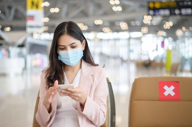 Una donna d'affari indossa una maschera protettiva all'aeroporto internazionale, viaggia sotto la pandemia covid-19,