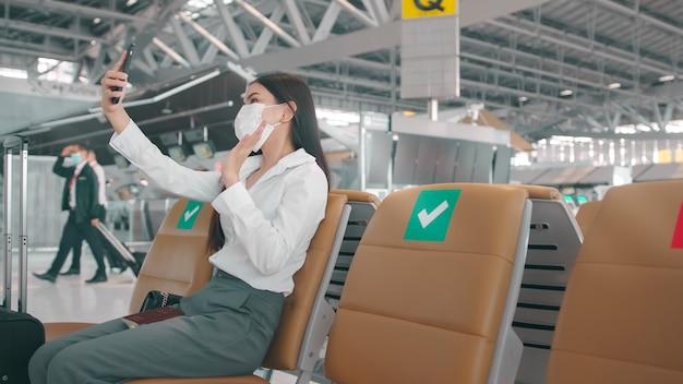 Una donna d'affari indossa una maschera protettiva all'aeroporto internazionale, le videochiamate alla sua famiglia viaggiano sotto la pandemia covid-19