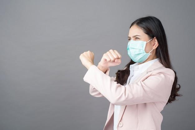La donna di affari sta indossando la maschera chirurgica, concetto di protezione di affari