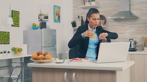 Donna d'affari in ritardo in ufficio mentre fa colazione. giovane libera professionista che lavora 24 ore su 24 per raggiungere i suoi obiettivi, stile di vita stressante, fretta, tardi al lavoro, sempre in fuga