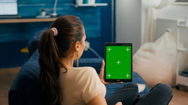 Donna di affari che esamina computer tablet con mock up display chroma key schermo verde seduto sul divano nel soggiorno. libero professionista che utilizza un dispositivo touchscreen isolato per la navigazione sui social network