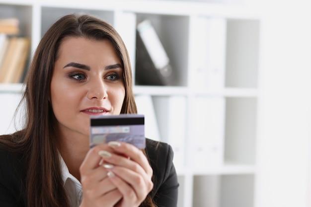 La donna di affari nell'ufficio tiene una carta di credito di plastica