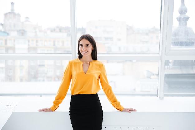 Donna d'affari in camicia arancione in piedi vicino alla finestra in ufficio e guardando la telecamera