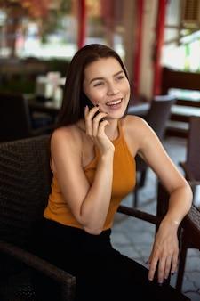 Donna d'affari fuori sede. la ragazza felice parla al telefono mentre è seduto al caffè.