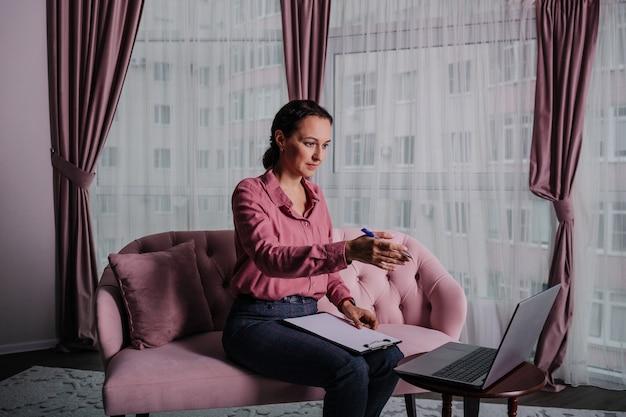 Una donna d'affari con una camicia rosa è seduta sul divano e sta conducendo una consultazione online su un laptop