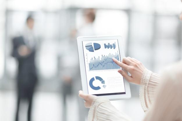 La donna di affari punta il dito contro lo schermo di una tavoletta digitale