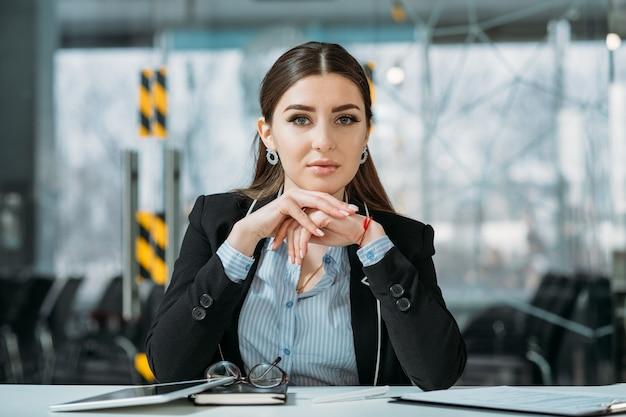 Ritratto di donna d'affari. ufficio di lavoro. premuroso dirigente aziendale con il mento appoggiato sulle mani.