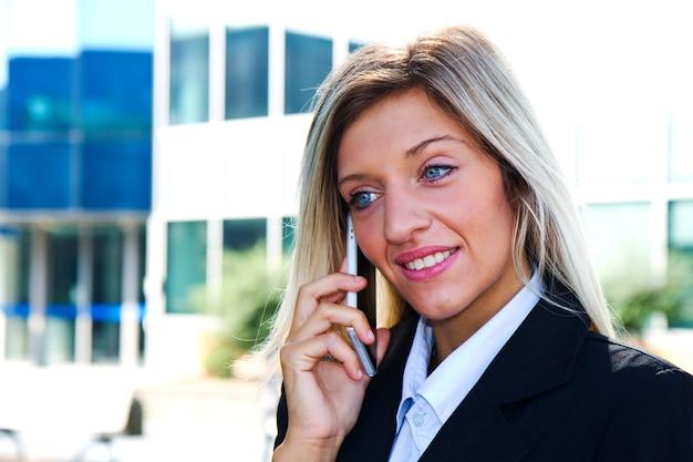 Ritratto di donna d'affari all'aperto che parla al telefono