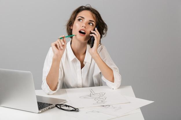 Donna d'affari in posa isolato sopra il muro grigio seduto al tavolo utilizzando laptop disegno e parlando per telefono