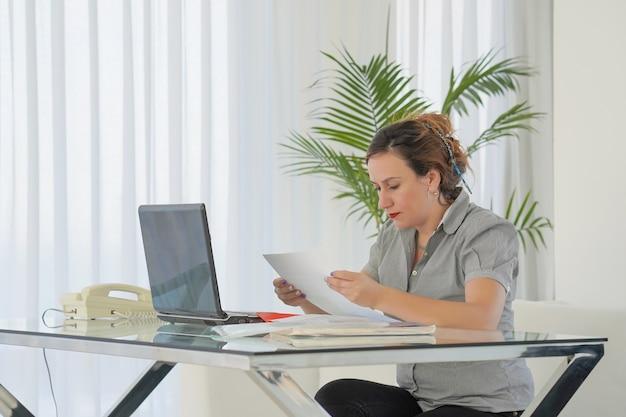 Donna di affari che legge un documento nell'area di lavoro dell'ufficio.