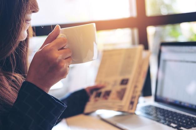 Una donna d'affari, leggendo il giornale, bevendo caffè e usando il portatile