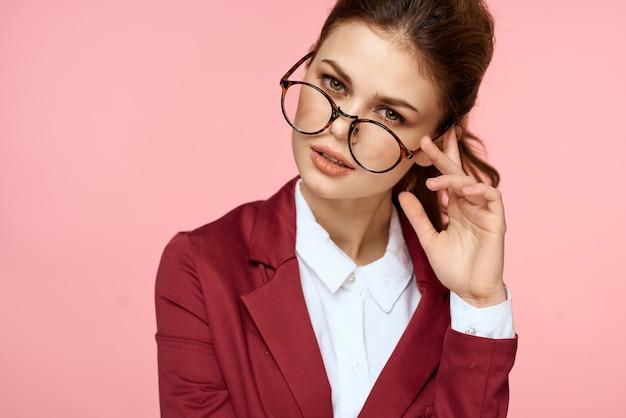 Business donna giacca rossa occhiali stile di vita esecutivo studio sfondo rosa.
