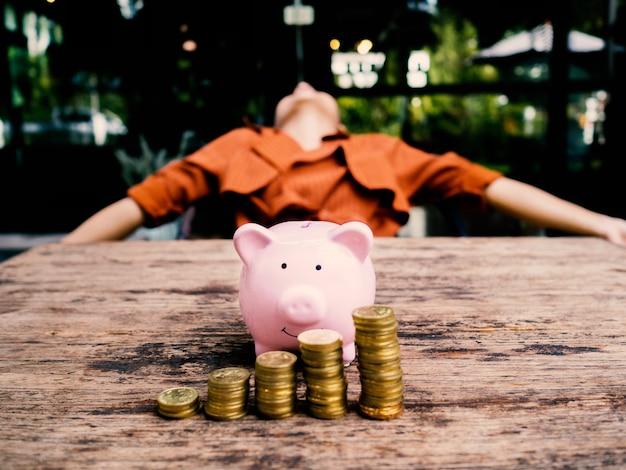 Donna d'affari che si rilassa dietro salvadanaio rosa con grafico di crescita del mucchio di monete d'oro, risparmio di denaro per il futuro piano di investimento e concetto di fondo pensione.