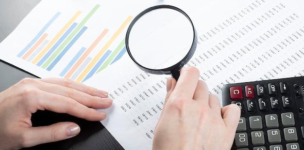 La donna di affari mostra al grafico con la calcolatrice e la lente d'ingrandimento