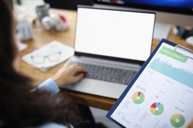 Una donna d'affari si siede a un laptop e guarda una pianificazione finanziaria di un rapporto statistico e