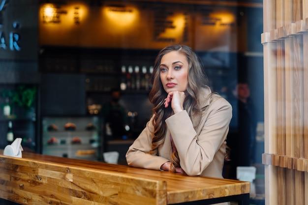 Business donna seduta cafe dietro la finestra in attesa di un partner commerciale femmina caucasica di riposo caffetteria bere caffè tardivo