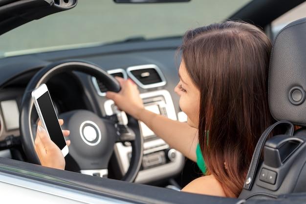 Donna di affari che si siede in automobile e che per mezzo del suo smartphone.