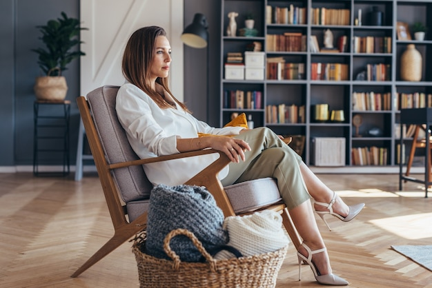 Donna di affari che si siede su una sedia a casa.