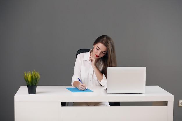 Business donna seduta a una scrivania con un computer portatile e guardando lontano in ufficio