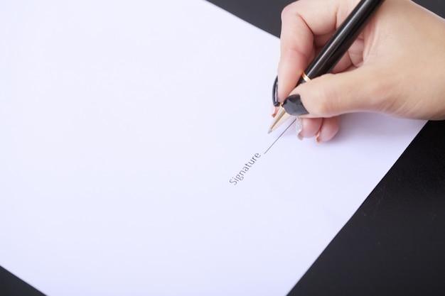 Donna di affari che si siede alla scrivania che firma un contratto con il fuoco basso sulla firma.