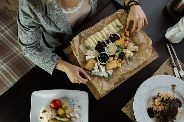 Business donna seduta a un tavolo in un ristorante e tiene in mano un piatto di formaggio