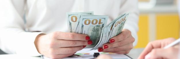 Donna d'affari seduta al tavolo con i colleghi e contando i soldi closeup contabilità ombra
