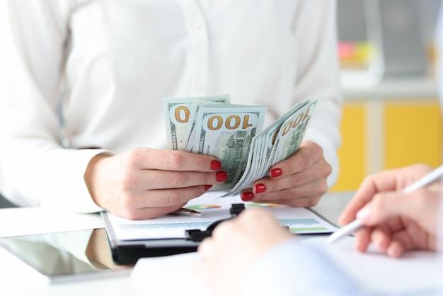 Donna di affari che si siede al tavolo con i colleghi e il conteggio dei soldi del primo piano