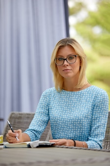 Donna di affari che sorride con il caffè ad una tabella sul terrazzo di estate