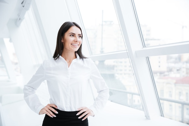Donna d'affari in piedi vicino alla finestra in ufficio con le braccia sui fianchi e guardando lontano