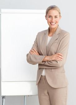 Donna di affari che si leva in piedi ad un bordo di presentazione