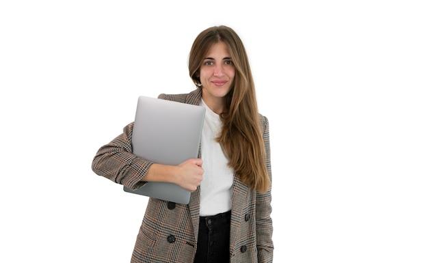 Donna d'affari in tuta tenendo il suo laptop con la mano, isolata su sfondo bianco.