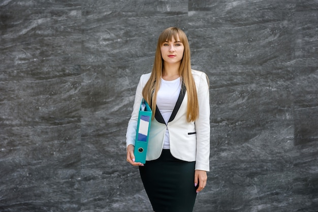 La donna di affari in vestito tiene una cartella nelle sue mani.
