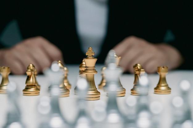 La donna di affari in un vestito gioca a scacchi. primo piano di una mano femminile su un concetto di business della concorrenza del gioco da tavolo di scacchi, messa a fuoco selettiva sui pezzi degli scacchi, concetto di business degli scacchi, leader e successo.