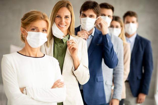 Donna di affari che toglie la sua maschera facciale protettiva e guarda la telecamera con i suoi membri del team