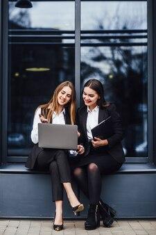 La donna di affari che parla per il business plan mentre si siede sul computer portatile! vicino al centro uffici!