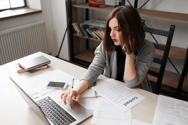 Donna di affari che comunica dal telefono cellulare all'ufficio