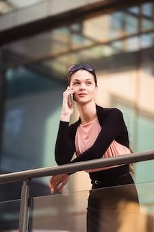 Donna di affari che parla al telefono durante una pausa caffè fuori dall'ufficio